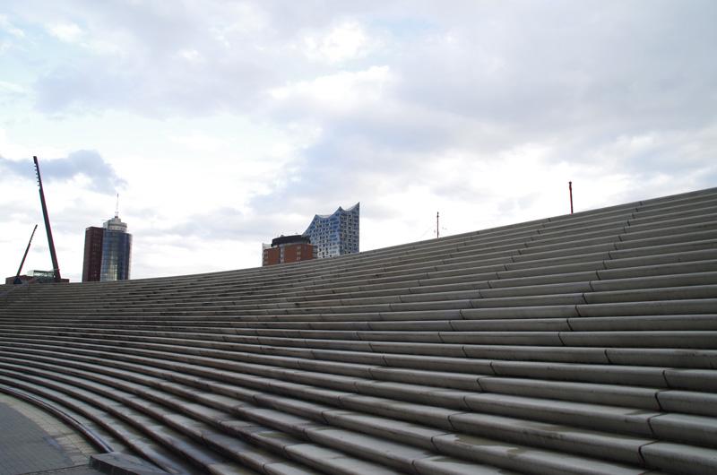 Hinter der neu gestaltenen Sturmflutmauer am Hamburger Hafen erhebt sich Elbphilharmonie.
