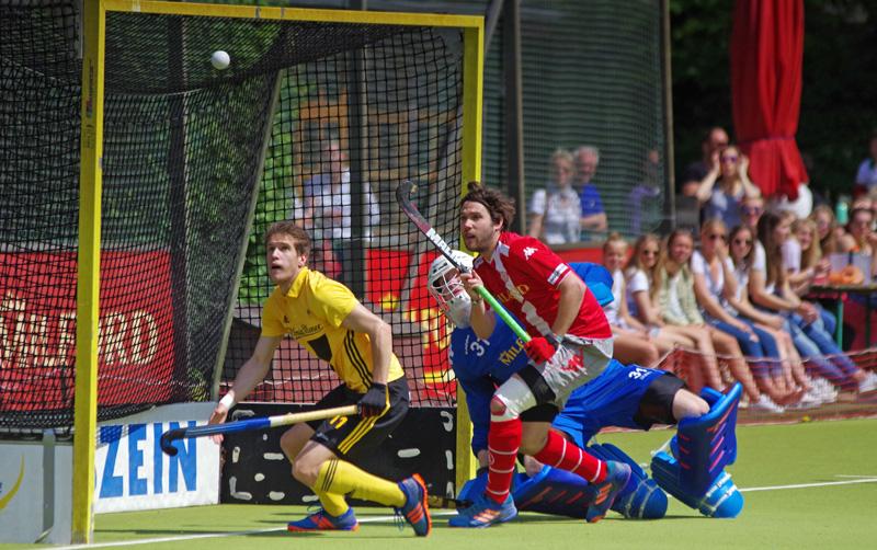 Die Kugel fliegt am Alster-Tor vorbei. Der einschussbereiten Leon Willemsen (HTHC). Torwart Felix Reuß und sein Mitspieler Patrick Müller (Club an der Alster) schauen dem Ball hinterher.