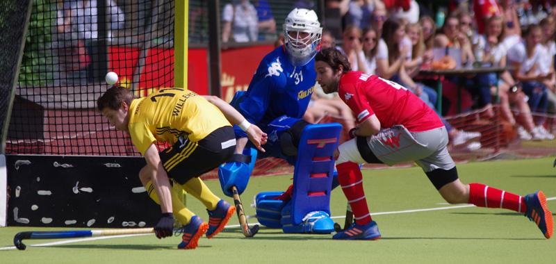 Die Kugel fliegt über den Rücken des einschussbereiten Leon Willemsen(HTHC). Torwart Felix Reuß und sein Mitspieler Patrick Müller schauen dem Ball hinterher