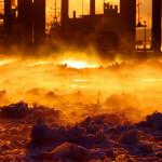 Winter im Hamburger Hafen. Im Licht der aufgehenden Sonne leuchtet das Eis auf der Elbe bronzefarben.