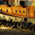 Rumpf und Aufbauten eines Schleppers im Hamburger Hafen reflektieren das Sonnenlicht.