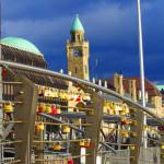 Liebesschlösser an einem Geländer an den Landungsbrücken im Hamburger Hafen.