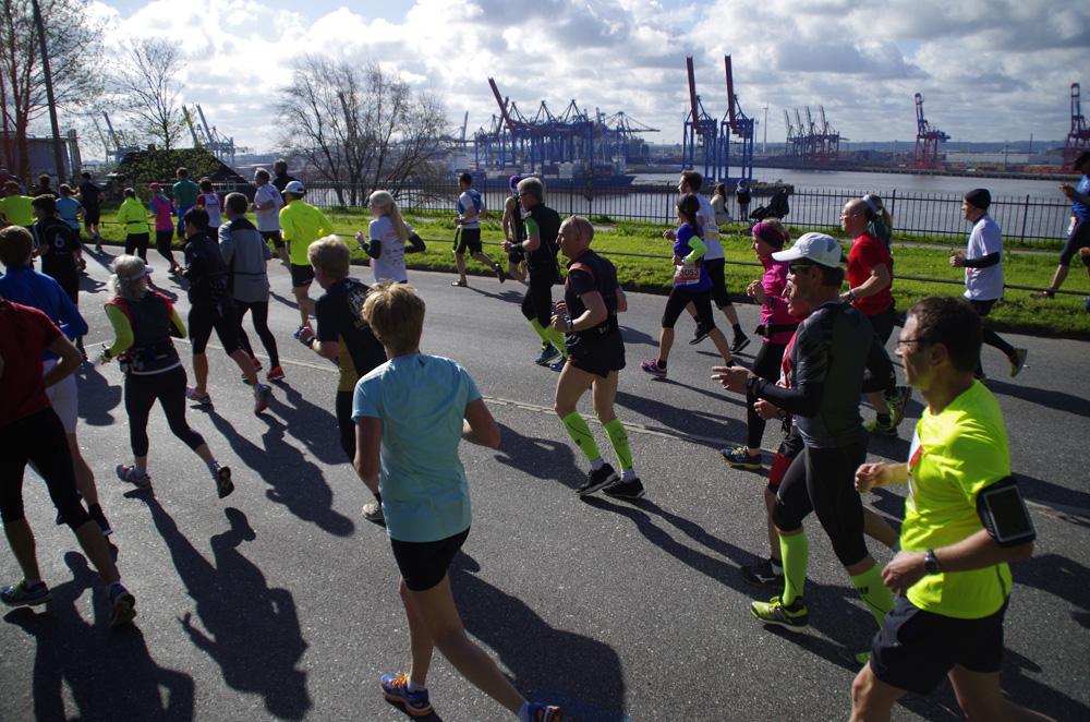 31. Haspa Marathon Hamburg: Läufer und Läuferinnen sind auf der Elbchaussee unterwegs. Im Hintergrund ist der Hamburger Hafen zu sehen.