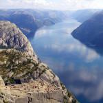 Wanderer sitzen auf dem Preikestolen und blicken auf den Lysefjord.