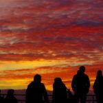 Abschied vom Goldenen Oktober: Besucher im Hamburger Hafen betrachten den farbenprächtigen Sonnenuntergang.