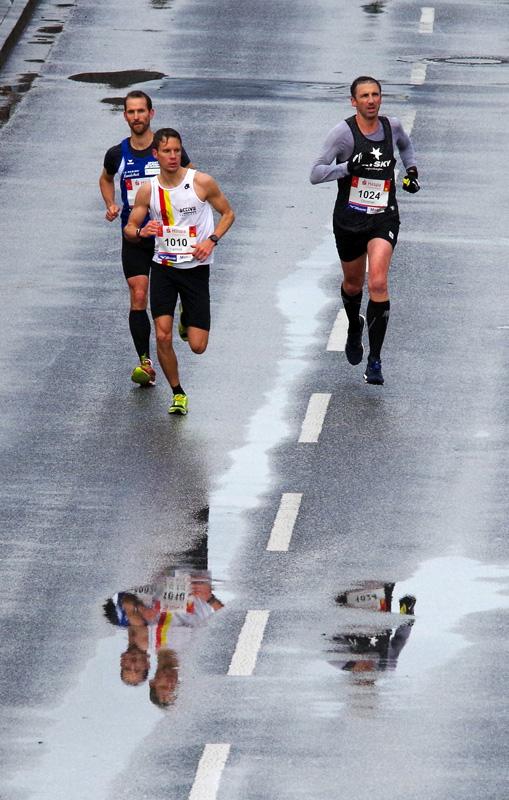 Läufer beim Haspa Marathon Hamburg spiegeln sich in einer Regenpfütze auf der Hafenstraße.
