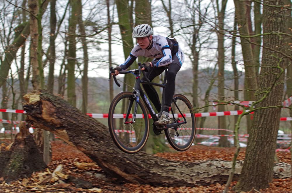 Radcross in Harburg: Ein Teilnehmer fliegt über einen Baumstamm.