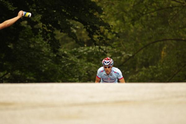 Ein Elite-Fahrer kurz vor dem Gipfel des Waseberges beim WorldTour-Rennen in Hamburg. Ein Helfer wartet mit einer Trinkflasche.