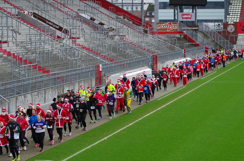 Santa Pauli statt Sankt Pauli: Kurz nach dem Start joggten die Weihnachtsmänner- und Frauen beim St. Pauli X-Mass-Run durch das Millerntor-Stadion, Heimspielstätte des Fußball-Zweitligisten FC St. Pauli.
