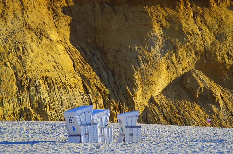Strandkörbe stehen vor dem dem Roten Kliff am Strand vor Kampen auf der Insel Sylt.