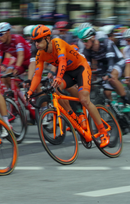 Die Profis biegen beim UCI WorldTour Rennen EuroEyes Cyclassics in Hamburg auf den Jungfernstieg ein. Zu sehen ist ein Fahrer des Teams CCC Sprandi Polkowice.