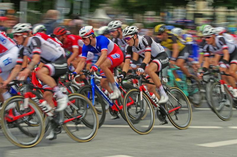 Die Profis biegen beim UCI WorldTour Rennen EuroEyes Cyclassics in Hamburg auf den Jungfernstieg ein.